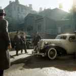 A screenshot from Mafia: Definitive Edition. Mafia guys hanging around a car