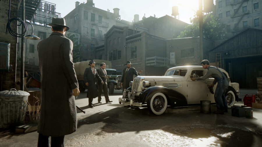 A screenshot from Mafia: Definitive Edition. Mafia guys hanging around a car