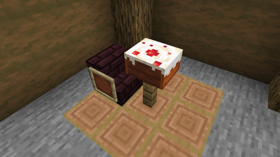A Cake in front of a chair in Minecraft.